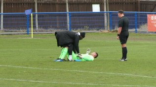 A thudding encounter leaves the goalkeeper in need of attention. A hard surface biting cold wind and rain.