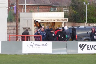 nearly half time . A line of spectators wneds its way toward the burger bar and the adjacent Lemonade Room