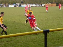 Two home players close in to take on one of the Wood players