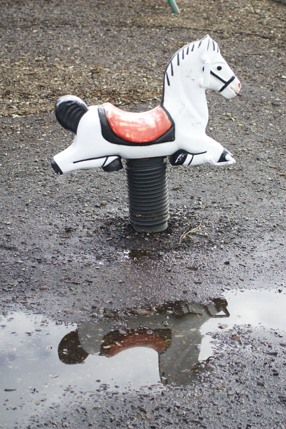 ride on horse at playground with a puddle of water