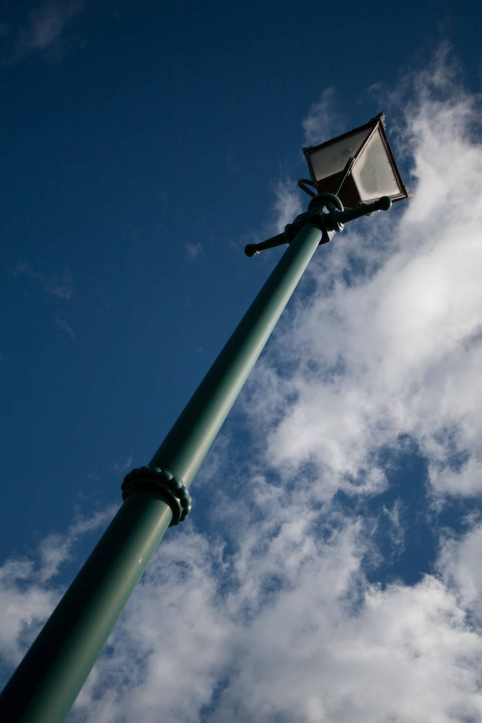 green lamp post against the blue sky