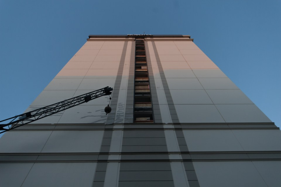 crane in front of a building ready to be knocked down