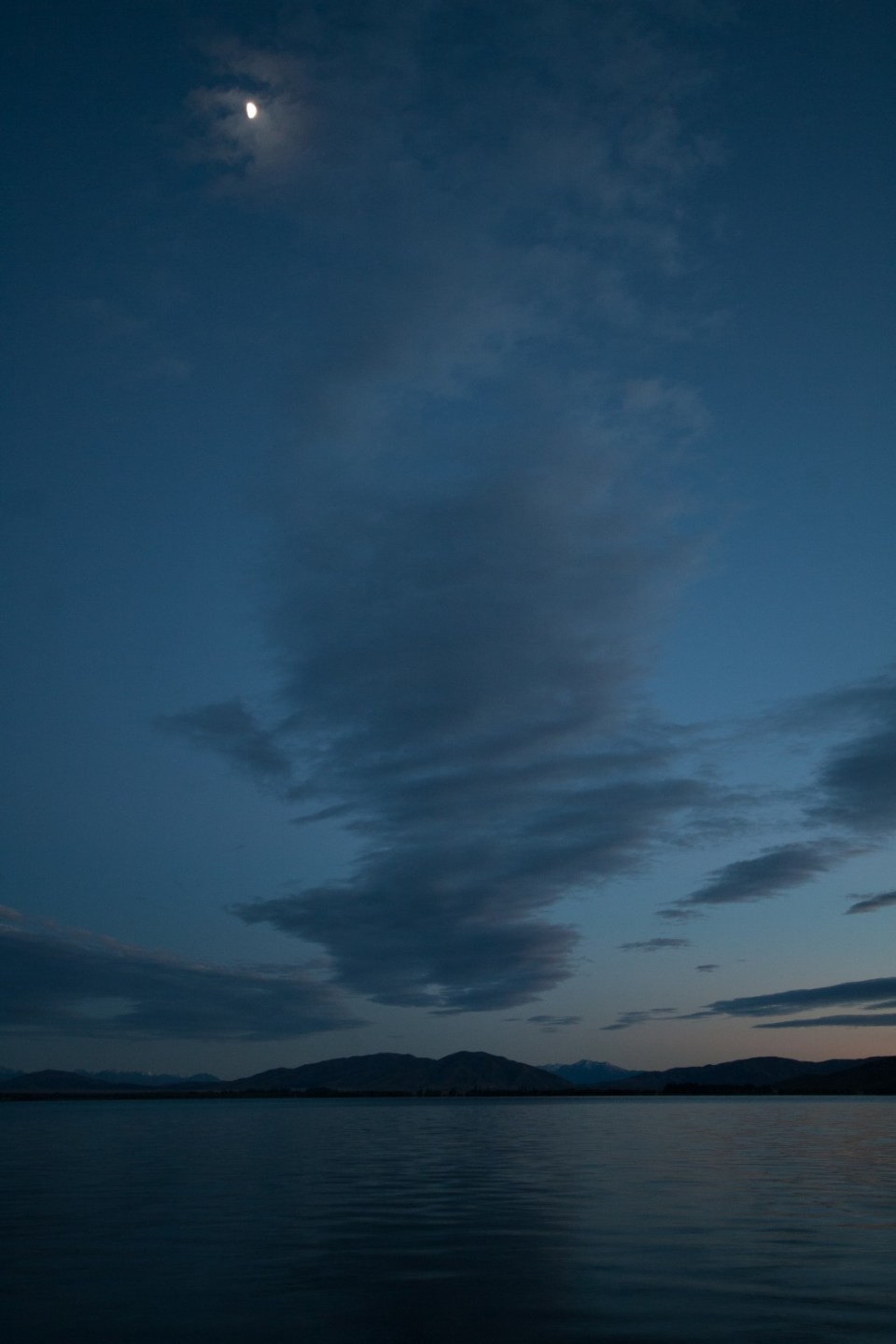 just before sunrise, view of lake and clouds with moon visible top of frame