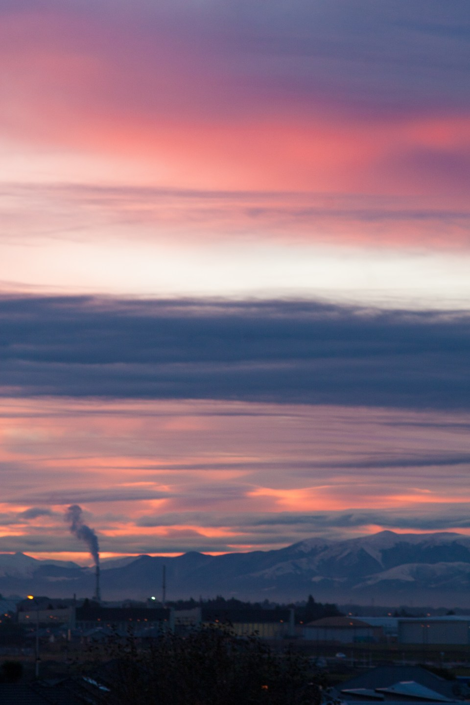 smoke stack against mountains and a pink sunset