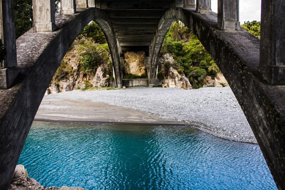 bridge span river blue water structure gravel arch
