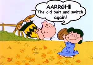"Lucy holding a football as Charlie Brown falls down after trying to kick it before Lucy moved it. Charlie Brown is saying, ""Aaargh!! The old bait and switch again."""