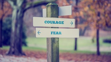 Retro style image of a rustic wooden sign in an autumn park with the words Courage - Fear offering a choice of reaction and attitude with arrows pointing in opposite directions in a conceptual image.
