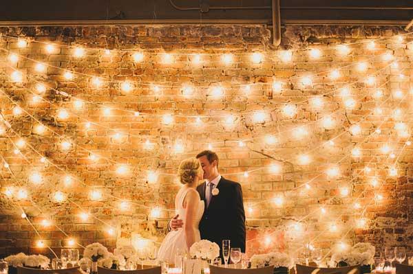 Bruidspaar met lichtjes op achtergrond