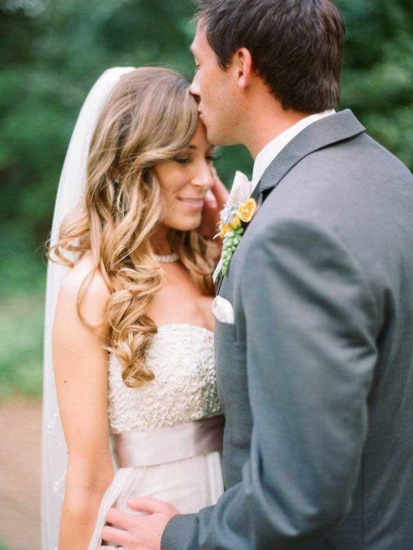 Bruid met los haar krijgt kus van bruidegom