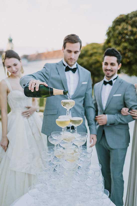 Bruidegom bij een champagne toren