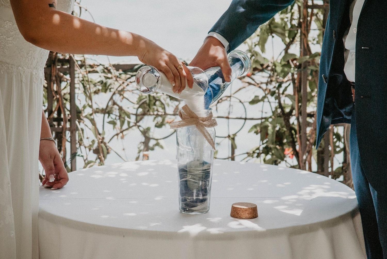 Bruidspaar giet zand in een vaas