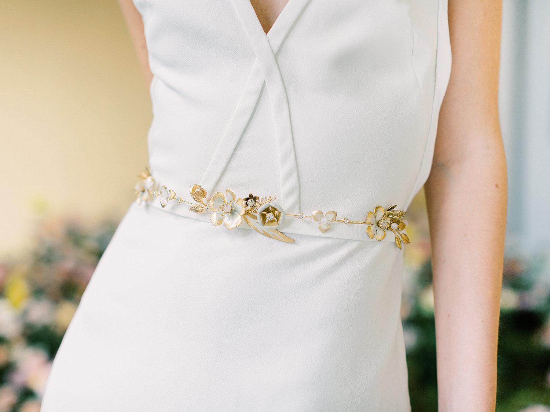 Bruid met gouden riempje om trouwjurk