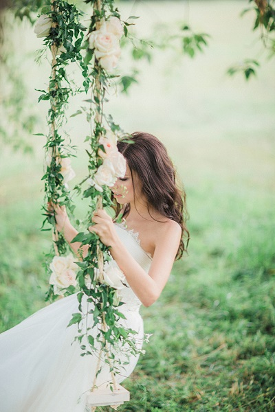 Bruid op schommel met bloemen