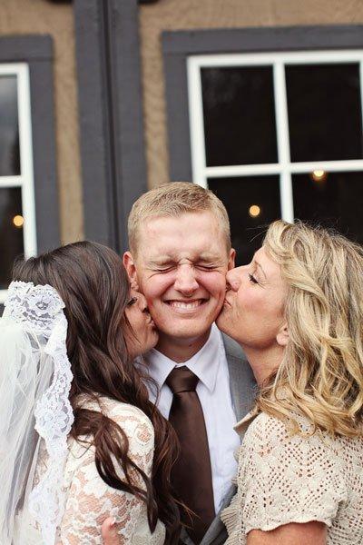 Bruid en schoonmoeder geven bruidegom een kus