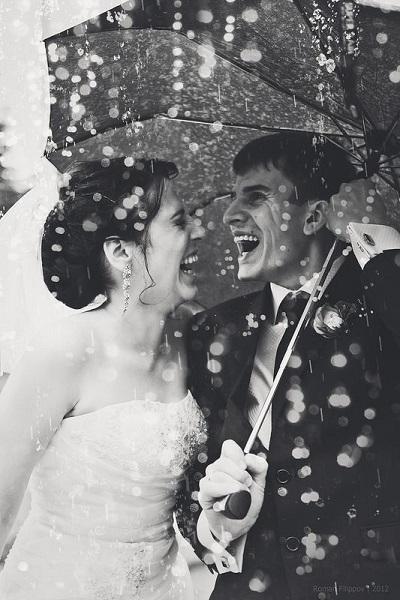 Bruidspaar in de regen onder paraplu