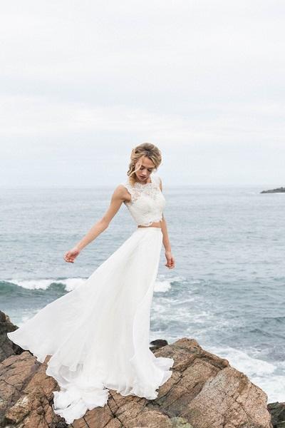 Bruid met two piece trouwjurk aan zee