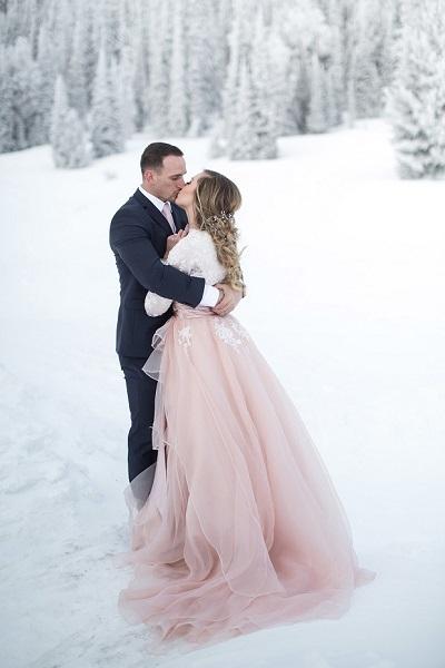 Bruidspaar in de sneeuw met prinsessenjurk