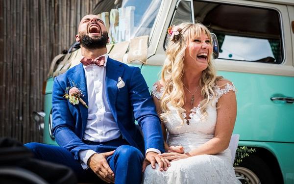 Goede trouwfotograaf legt lachend bruidspaar spontaan vast