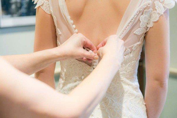 Bruid is trouwjurk aan het passen