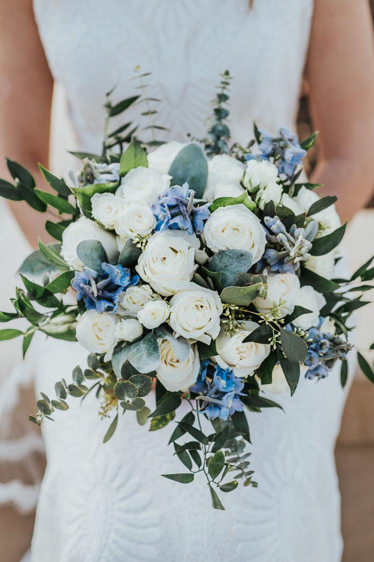 Bruid met blauwe bloemen in haar bruidsboeket