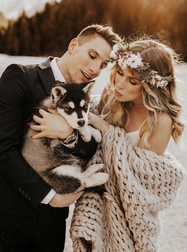 Bruidspaar op winterbruiloft met puppy