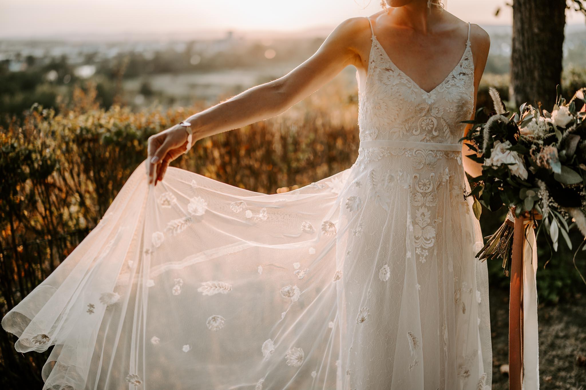 Bruid met trouwjurk in haar handen