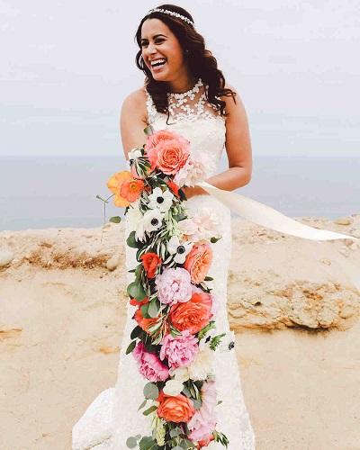 Bruid met roze bloemenslinger