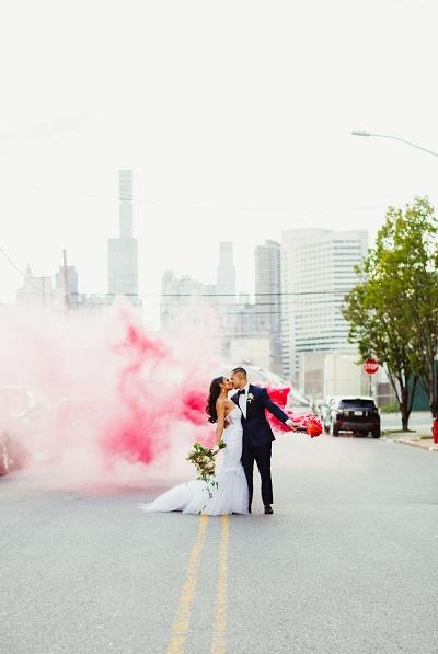 Bruidspaar met gekleurde rookbom op de weg