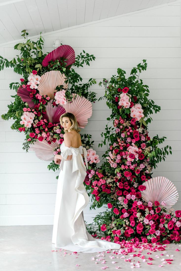 Bruid met roze bloemen als backdrop