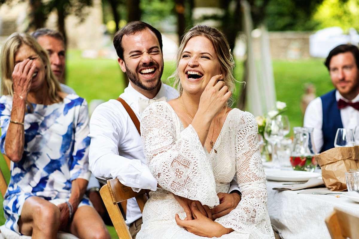 Lachend bruidspaar tijdens een speech op hun bruiloft