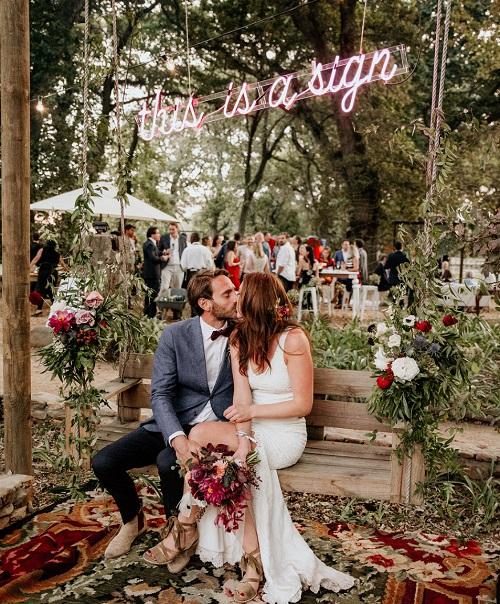 Bruidspaar met roze neon letters
