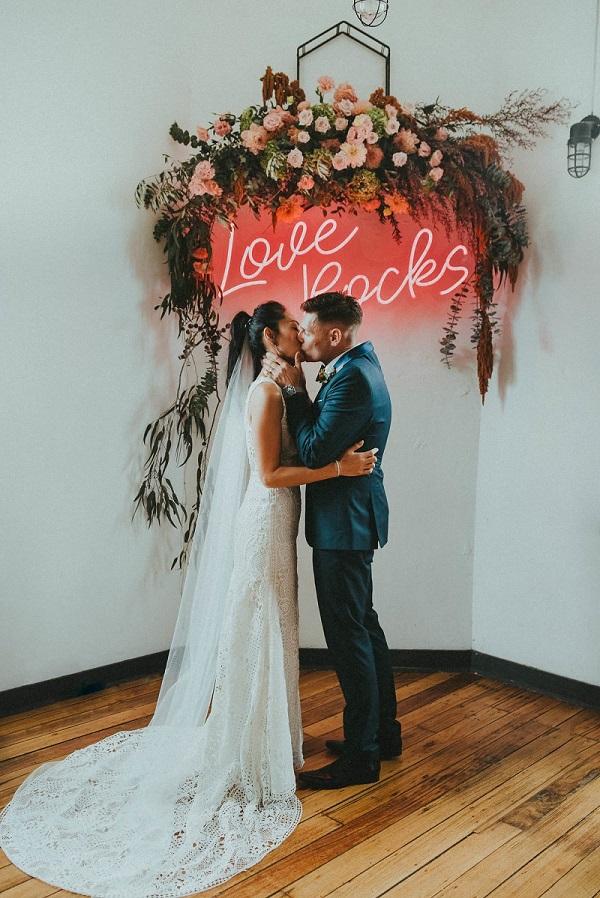 Bruidspaar kust onder neon sign