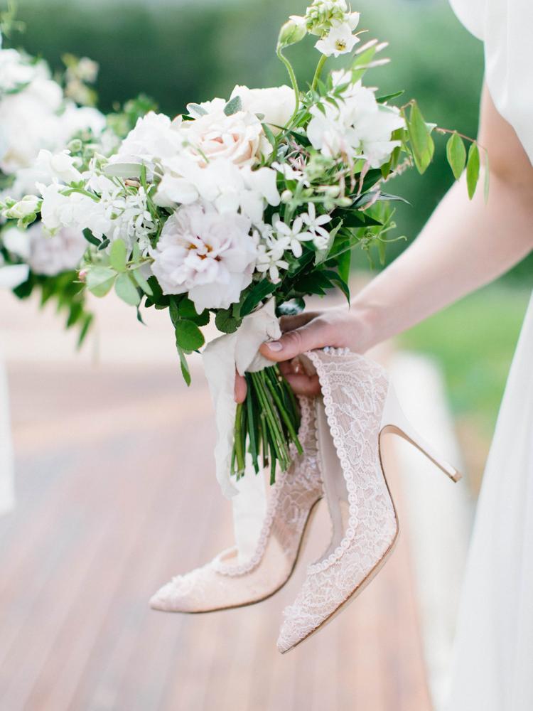 Bruid met trouwschoenen in haar hand