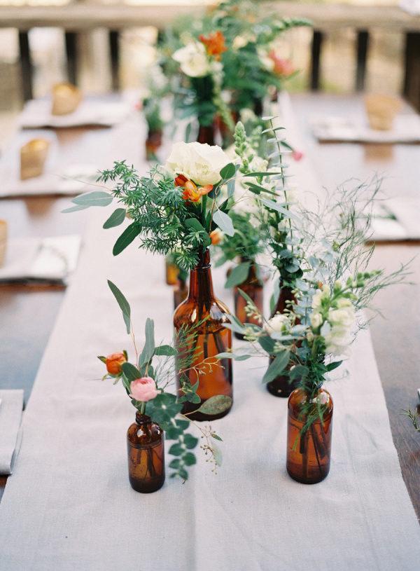 Glazen flesjes met bloemen als decoratie