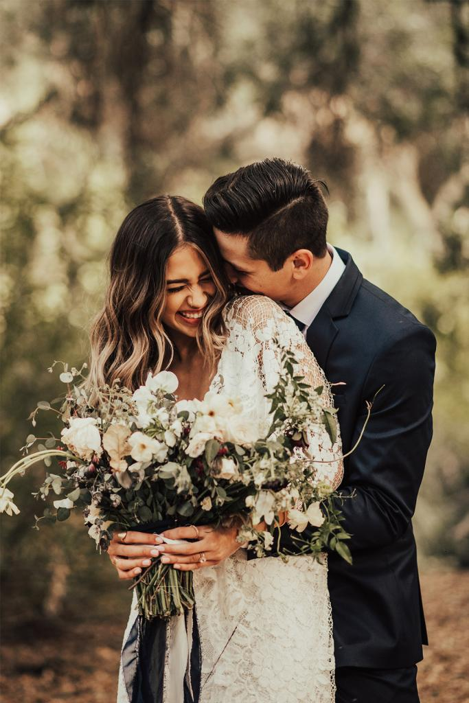 Lachend bruidspaar met bruidsboeket