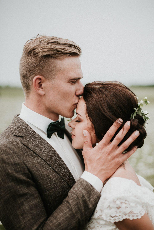 Bruidegom kust bruid op haar voorhoofd