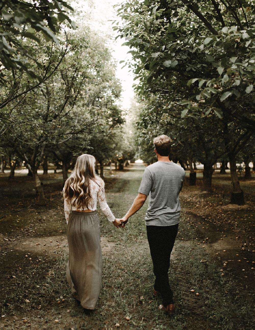 Stel hand in hand tussen de bomen