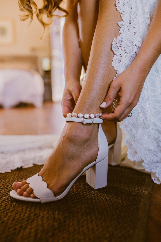 Bruid trekt haar bruidsschoenen aan