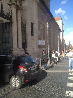 The black car in this photo is driving into the Vatican City. There are two armed Swiss Guards who stand at the gate. Tourists can't enter here.