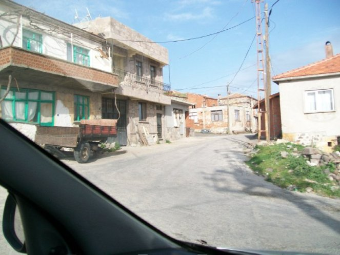View from a car into a small village with run down buildings.