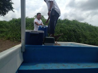 Two men stand at the prow of the river boat on the way back from Tortuguero.