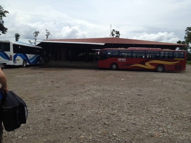 Two tour buses parked outside a shelter near Tortuguero.