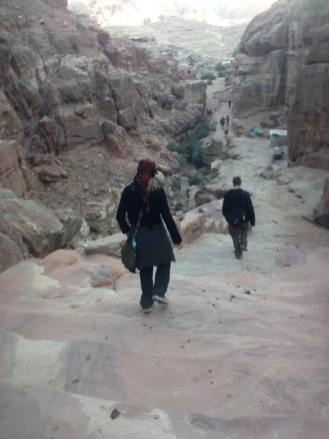 At Petra in Jordan, Lydian and John walk down some stairs as the sun sets.