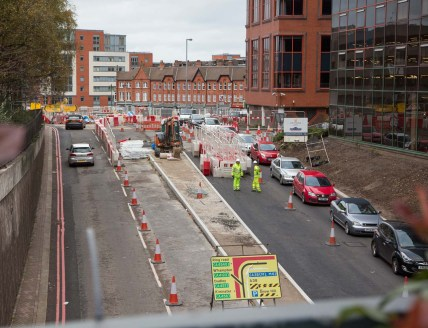 Looking back (north) to where the road swings right round to Great Charles Street with entrance to Cambridge Street top left.