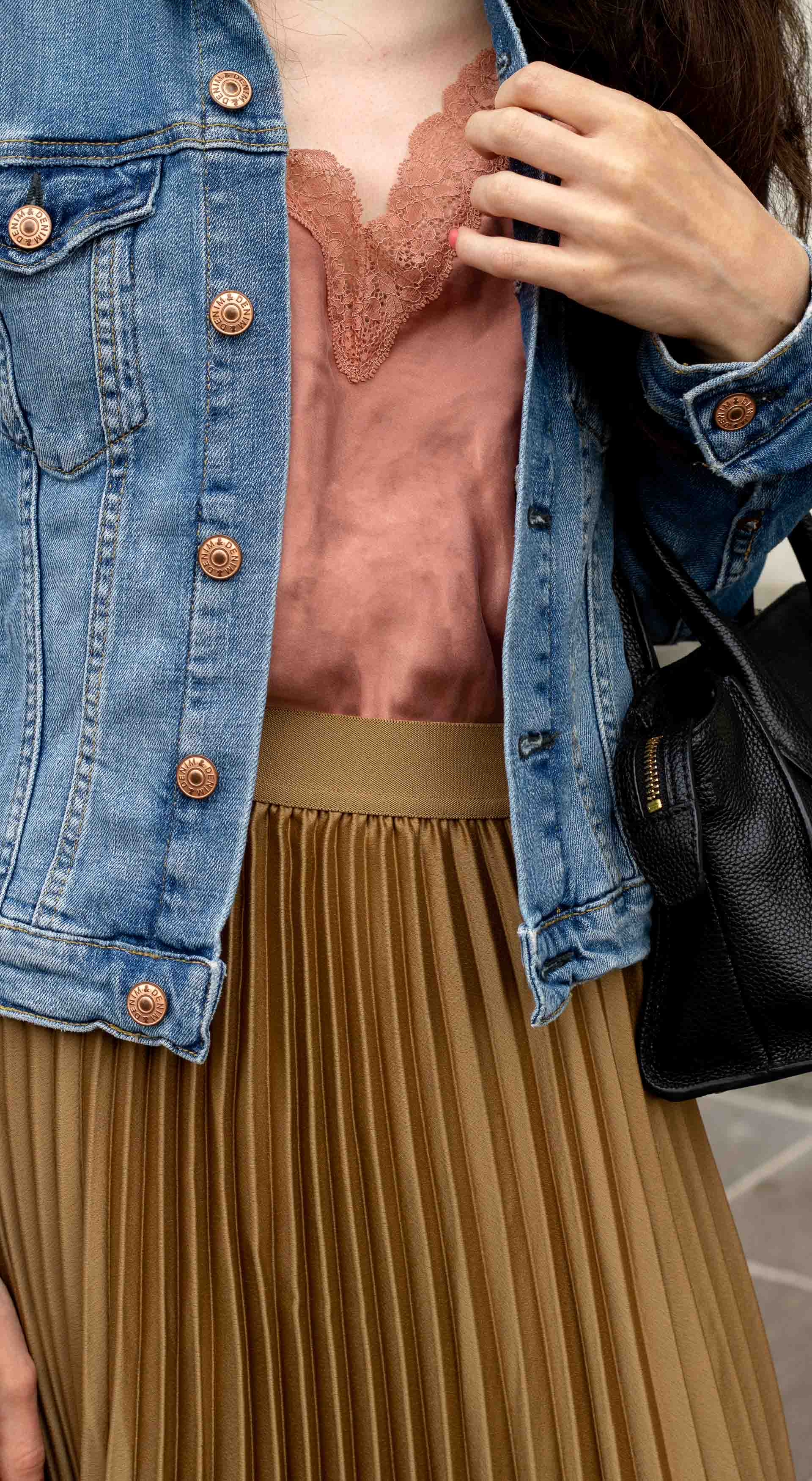 Fashion blogger Veronika Lipar of Brunette from Wall Street dressed in casual summer to fall outfit H&M denim jacket Etam slip top H&M gold pleated midi skirt