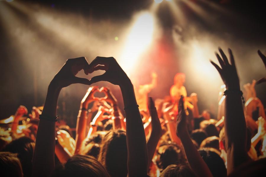 Foto van een feest met mensen die een hartje maken met hun handen