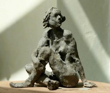 Dalila, assise, jambe gauche au dessus de la droite tenue par la main droite, en appui sur le bras gauche