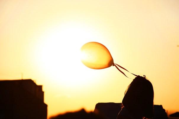 Una niña hace volar un globo sobre el ocaso del Sol. Bruno Ramos, periodista