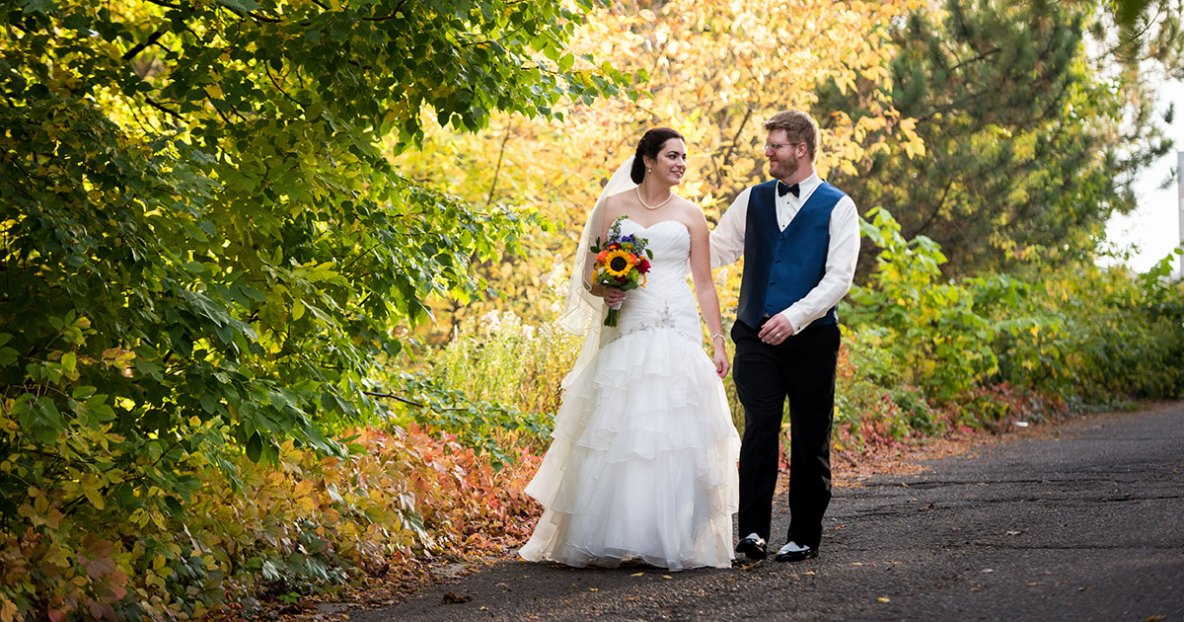 Bride and groom portrait outside walking on a nature lined path.