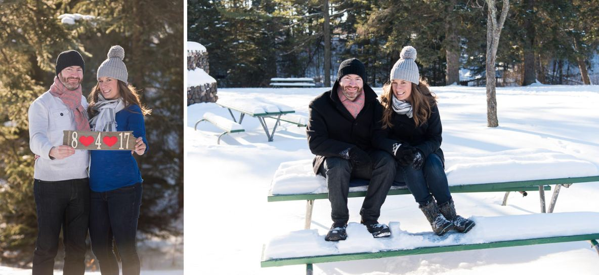 Engaged couple in snowy landscape, sitting on a picnic bench.